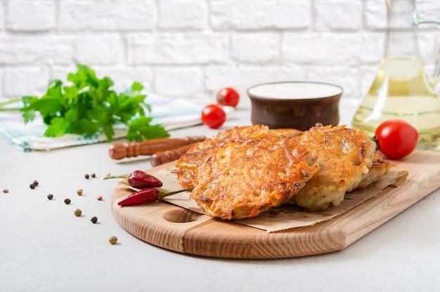 Frittelle di patate appena cotte con panna acida su una tavola di legno sul tavolo della cucina. piatto vegetariano