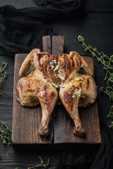 Pollo arrosto appena cucinato con erbe aromatiche, su tavolo di legno nero