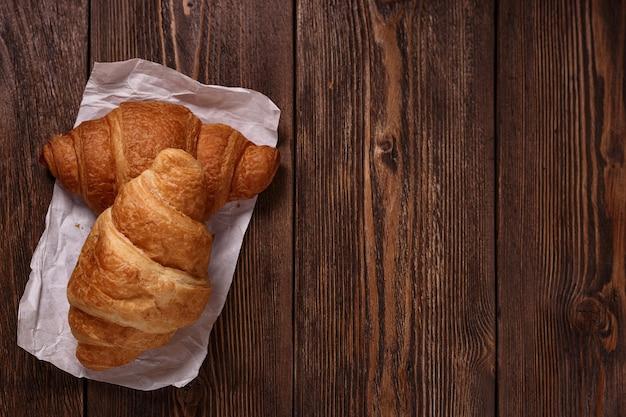 Croissant freschi su carta bianca sul tavolo di legno scuro. dessert dolce e gustoso. concetto di cottura vista dall'alto con posto vuoto per il testo.