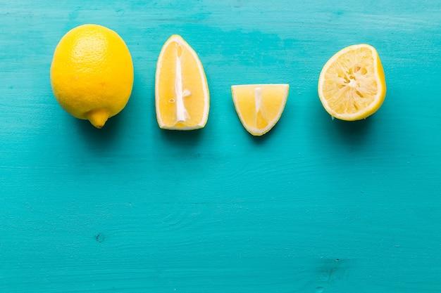 Appena tagliato metà e interi limoni su fondo rustico acquamarina