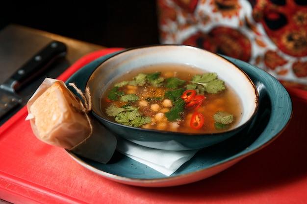 Zuppa aromatica di ceci e carne appena fatta condita con prezzemolo. Foto Premium