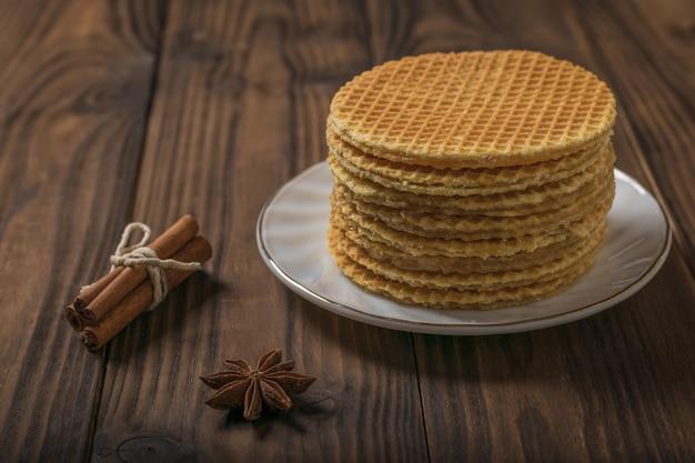 Cialde fatte in casa appena fatte con crema di cannella e caramello su un tavolo di legno. torte fatte in casa con spezie.