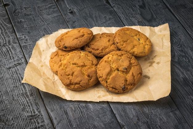 Biscotti di farina d'avena appena fatti su carta su un tavolo di legno nero