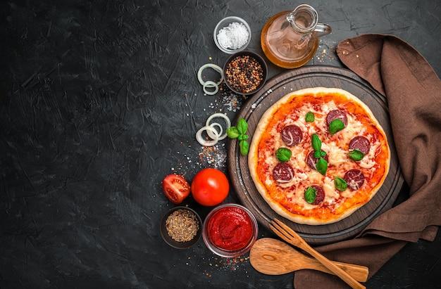 Pizza ai peperoni appena fatta, pomodori, salsa di pomodoro, cipolle e spezie su uno sfondo nero. vista orizzontale con spazio per copiare.