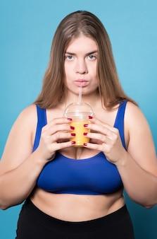 Appena fatto. ragazza grassoccia abbastanza giovanile che beve il succo d'arancia.