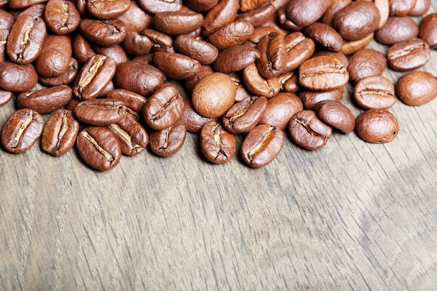 Chicchi di caffè appena tostati naturali sopra fondo di legno strutturato.