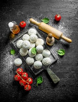 Gnocchi di manta crudi di preparazione fresca sulla tavola rustica nera