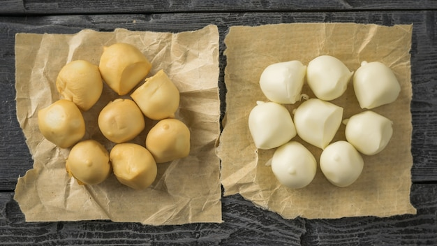 Mozzarella affumicata e regolare appena preparata in carta su una tavola di legno nera