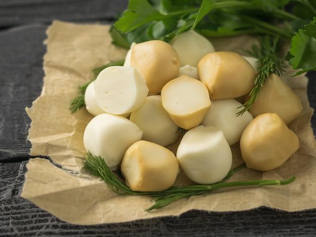 Mozzarella affumicata e regolare appena preparata in carta su una tavola di legno