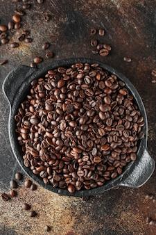 Chicchi di caffè appena tostati in una piccola padella nera