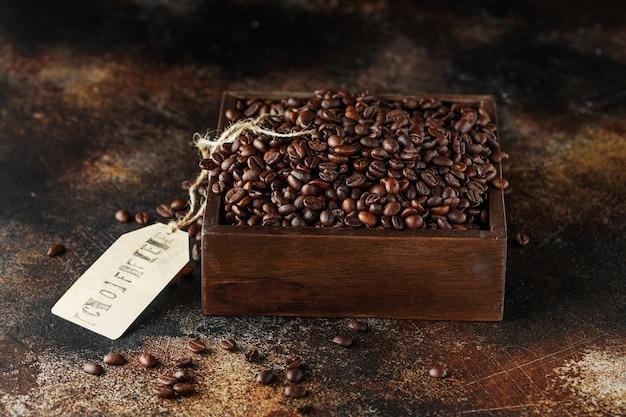 Chicchi di caffè appena tostati in una scatola di legno
