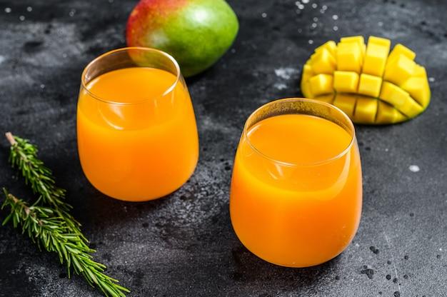 Succo di mango appena spremuto in un bicchiere. sfondo nero. vista dall'alto