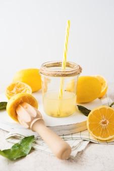 Succo di limone naturale appena spremuto in un barattolo di vetro su uno sfondo bianco, fuoco selettivo