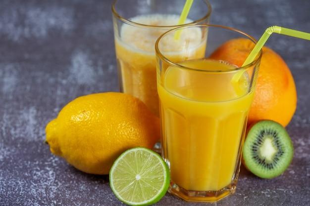 Succo d'arancia appena spremuto e frullati di banana e arancia in bicchieri alti con una cannuccia circondata da frutti su uno sfondo grigio cemento. il concetto di dimagrimento, porta la figura in forma.