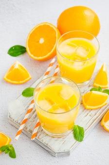 Succo d'arancia appena spremuto con ghiaccio in un bicchiere con una cannuccia su una tavola di legno su una superficie leggera con arance fresche. orientamento verticale, da vicino.