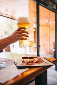 Birra appena spillata. barista che tiene in mano un bicchiere di birra appena spillato