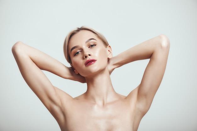 Freschezza giovane donna sana che tiene le braccia in alto e mostra le ascelle pulite mentre sta in piedi contro