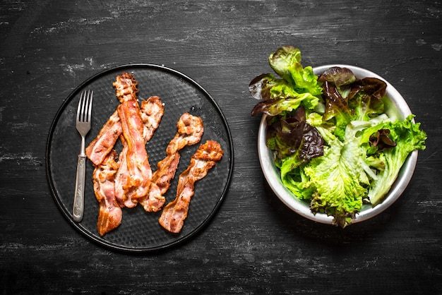 Pancetta fritta con verdure. su uno sfondo di legno nero.