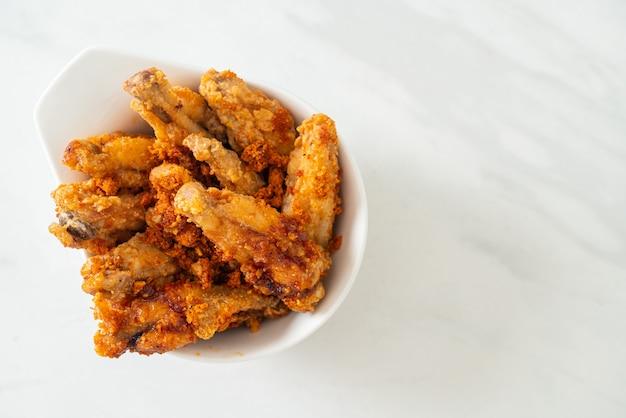 Ali di pollo fritte al barbecue in una ciotola bianca