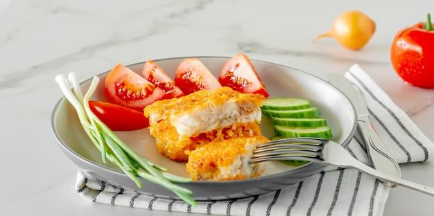 Filetti di pesce fritti impanati withcucumper ant pomodori serviti su un piatto da vicino.