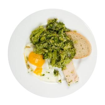 Broccoli fritti con uovo e salsiccia sulla zolla bianca isolata. vista dall'alto