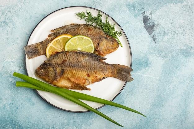 Carpa fritta di pesce su un piatto con fette di limone e lime, con verdure su sfondo blu. pasto pronto. copia spazio