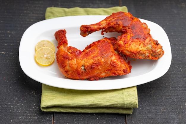 Coscia di pollo fritta o coscia di tamburo friggere il pollo indiano piccante con sfondo nero