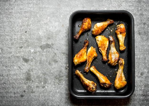 Cosce di pollo fritte sulla teglia. sul tavolo di pietra.