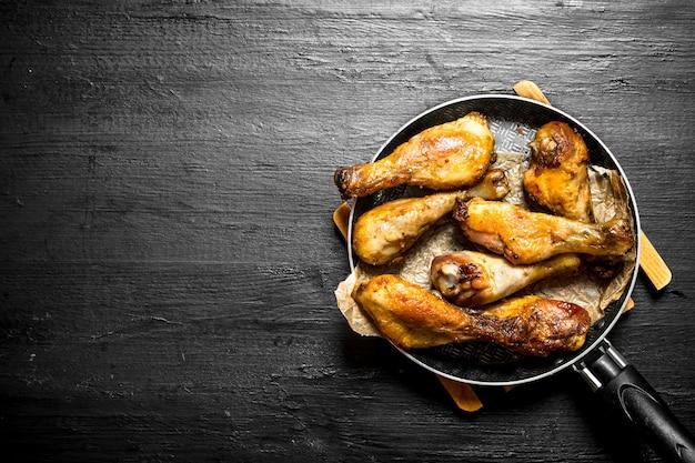Cosce di pollo fritte in padella. su uno sfondo di legno nero.