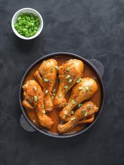 Cosce di pollo fritte con curry in una vecchia padella in ghisa.