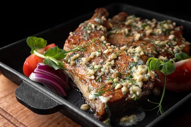 Cosce di pollo fritte con aglio, cipolle ed erbe aromatiche, in una padella nera