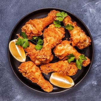 Cosce di pollo fritte con limone e prezzemolo. vista dall'alto