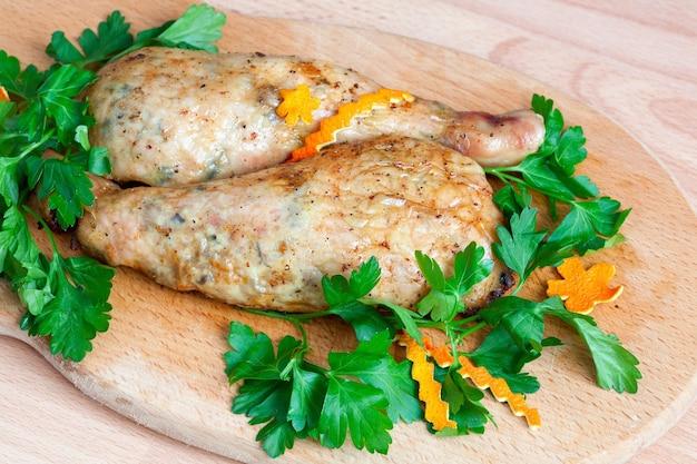 Cosce di pollo fritte con prezzemolo sulla tavola.