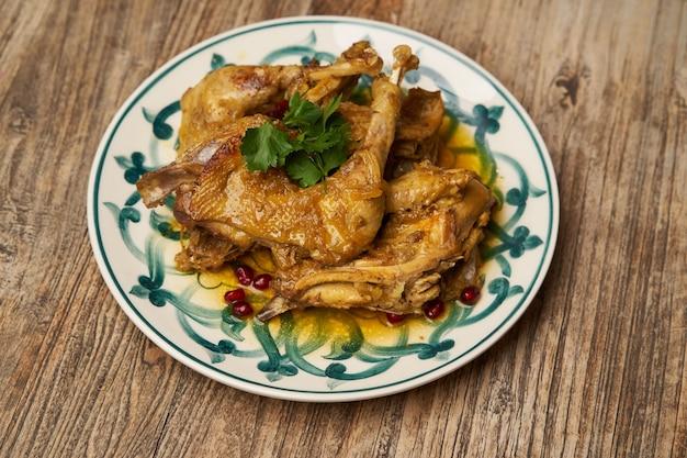 Cosce di pollo fritte con melograno e prezzemolo sul fondo della tavola in legno con spazio di copia, vista dall'alto