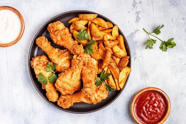 Cosce di pollo fritte con patate. vista dall'alto