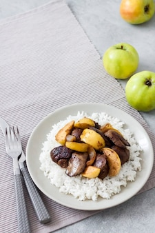 Fegato di pollo fritto con mele servito con riso bianco su un piatto. mele verdi in superficie. copia spazio