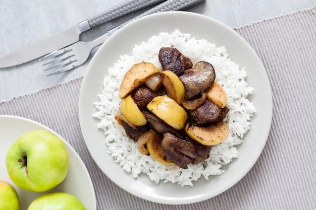 Fegato di pollo fritto con mele servito con riso bianco su un piatto. mele verdi in superficie. vista piana laico e dall'alto