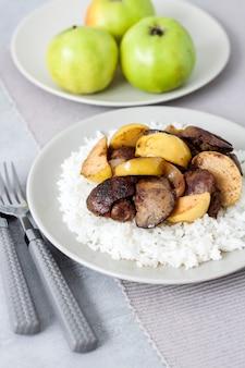 Fegato di pollo fritto con mele servito con riso bianco su un piatto.