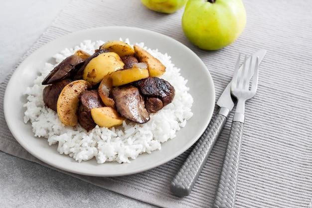 Fegato di pollo fritto con mele servito con riso bianco su un piatto