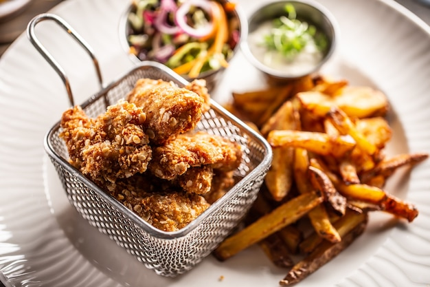 Pepite di pollo fritte in cestino di metallo servite con patatine fritte su un piatto bianco.