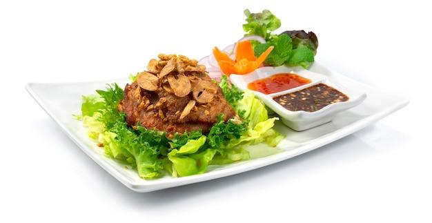Pollo fritto in cima aglio croccante stile thailandese servito salsa al peperoncino decorare carote intagliate e verdure sideview
