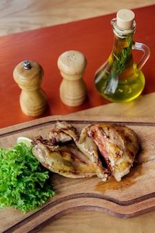 Le parti di pollo fritto sono su tavola di legno con insalata, pomodori, olio e spezie