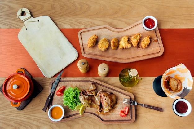 Le parti e le pepite di pollo fritto sono sul bordo di legno servito con insalata, pomodori, olio e spezie