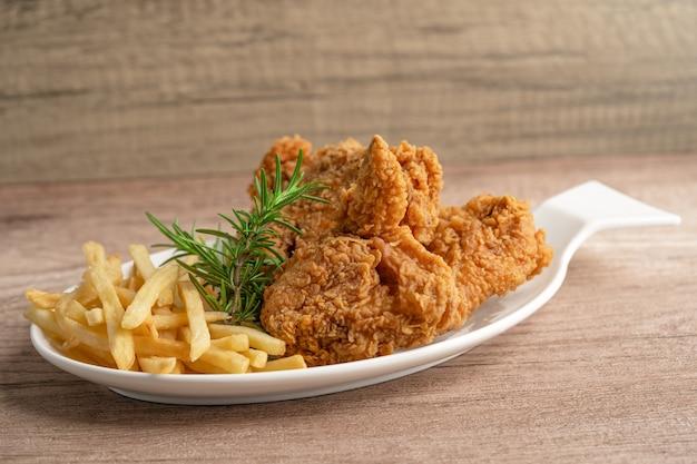 Pollo fritto e patatine con foglia di rosmarino, cibo spazzatura ad alto contenuto calorico servito su piatto bianco