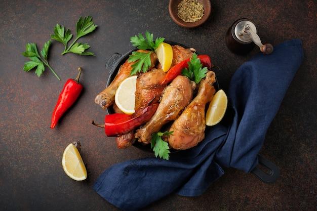 Stinchi appuntiti di pollo fritto in una padella di ghisa su uno sfondo scuro di cemento o pietra