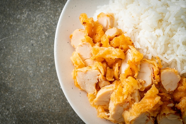 Pollo fritto ricoperto di riso con salsa piccante spicy