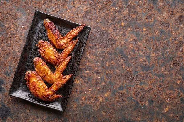 Alette di pollo fritte in piatto di ceramica rettangolare nero su sfondo arrugginito con copia spazio per il testo, vista dall'alto