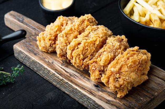 Parti di ali di pollo fritte sulla tavola di legno nera