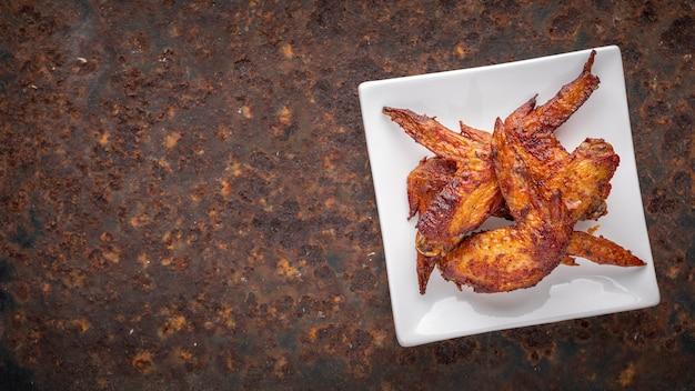 Alette di pollo fritte in piatto di ceramica quadrato bianco su sfondo arrugginito con copia spazio per testo, vista dall'alto, rapporto full hd