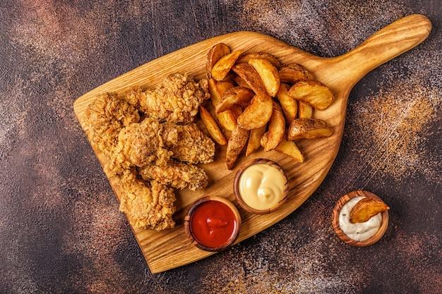 Alette di pollo fritte con fette di patate fritte, vista dall'alto.